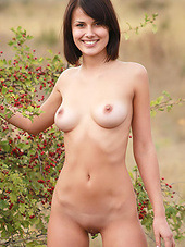 Beautiful young lady with sexy natural tits models her hot body outdoors